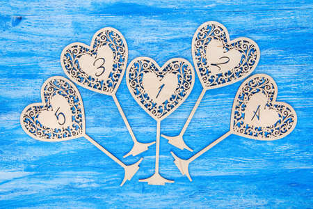 3 4: wooden figures 1,2,3,4,5 in the form of hearts carved on a blue wooden background Stock Photo