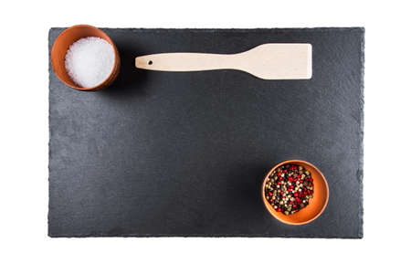 peppar: multicolored peppers and salt in a clay cup on a slate board, wooden kitchen spatula, top view, isolated