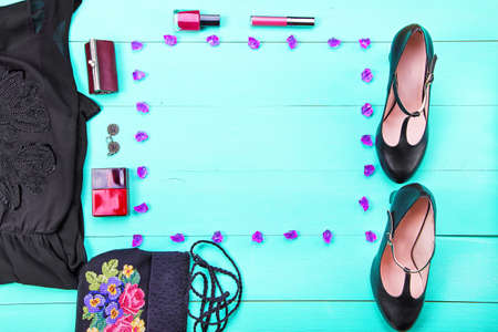 tacones negros: womens clothes - dress, embroidered bag, black heels, earrings, nail polish, lipstick. turquoise wooden background, top view Foto de archivo