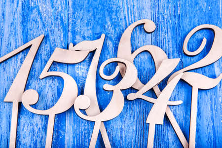 top seven: wooden numbers one, two, three, four, five, six, seven, scattered on a blue wooden background, top view