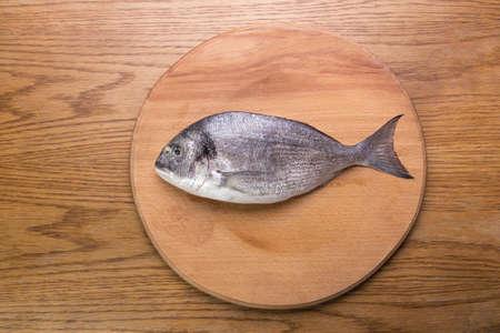dorado fish: dorado fish on a wooden board, top vew Stock Photo