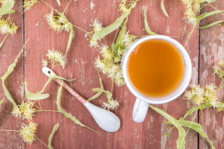 Linden tea in a cup on a wooden background. Around scattered fragrant linden flowers. view from above