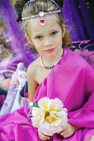 small European girl in oriental dress, crimson color, with rose, in a tent outdoors, harmony, staged shooting