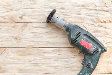 burnish: attachment on a drill, scrape, metal rotating brush. attachment is on a rough wooden surface