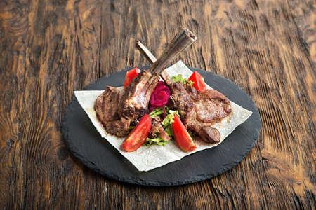 carne asada: chuletón de carne en el hueso, hacha de guerra, sirvió con los tomates y la lechuga iceberg en pita a bordo de pizarra. Foto de archivo