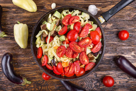 eating utensil: Sliced fresh vegetables in pan with spices and ingredients on wooden table, top view