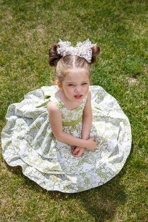 capricious: little dissatisfied girl in a dress with two bows sitting on the grass. her face unhappy. Girl tired. top view
