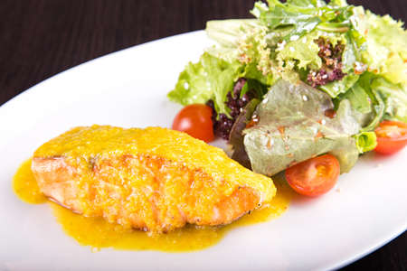 fillet of salmon fish and cheese on a plate with lettuce, arugula and cherry tomatoes with sesame seeds.