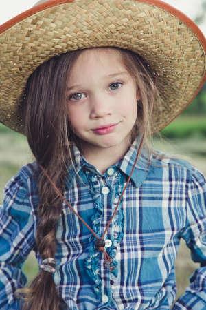 in the field is little beautiful girl Cowboy. facial portrait