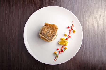 pikeperch: cooked fish fillet of pike-perch on a bed of onion served with a lemon and red currant