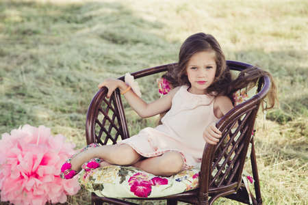 upbringing: beautiful little girl with flowing hair sitting in a wicker chair. a girl wearing a pink dress. in the background is the field