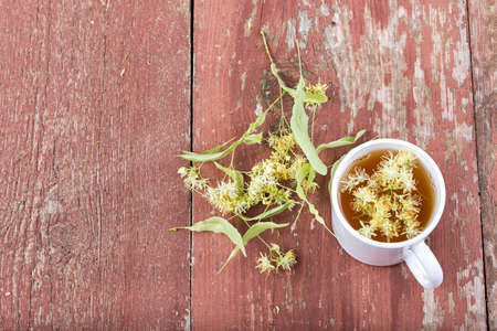 linden tea: Linden tea in a cup on a wooden background. Around scattered fragrant  flowers. view from above Stock Photo