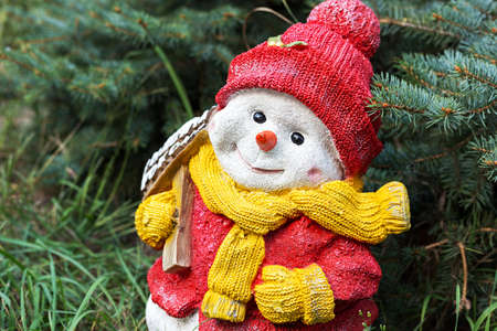 Snowman toy on the grass under the spruce, the celebration of Christmas in a warmer climate