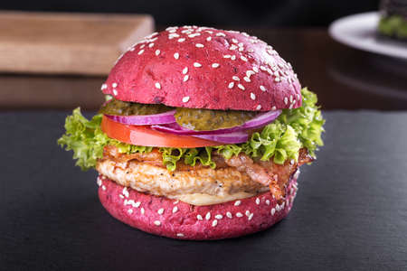 Red burger with cutlet, bacon and vegetables, sprinkled with sesame seeds on a blackboard
