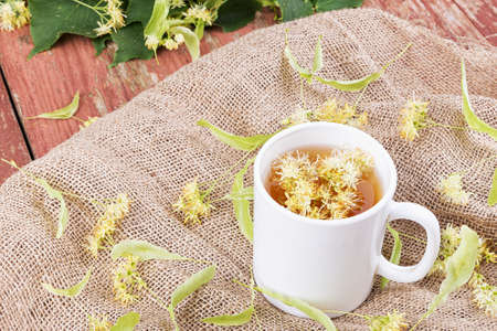 linden tea: Linden tea in a cup on a wooden background. Around scattered fragrant linden flowers