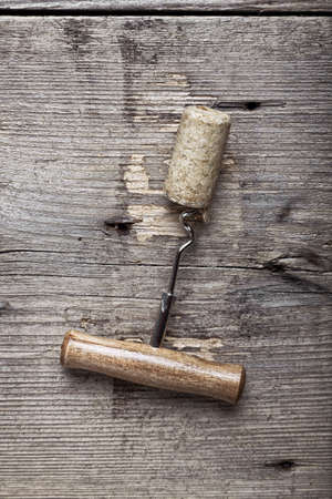 uncork: cork and corkscrew on a grunge wooden background. top view