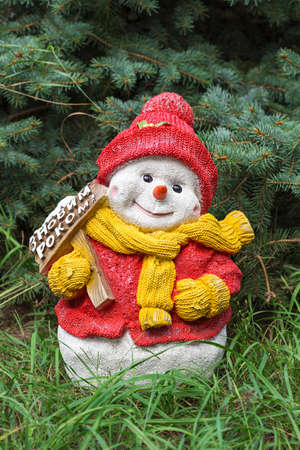 warmer: Snowman toy on the grass under the spruce, the celebration of Christmas in a warmer climate