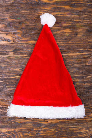 red Santa Claus hat on a wooden background, Christmas and New Year, New Year holidays