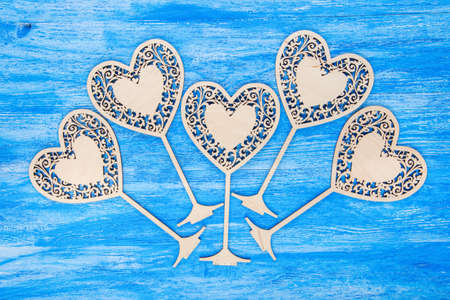 carved wooden hearts on Valentines Day, with space for text on a blue wooden background