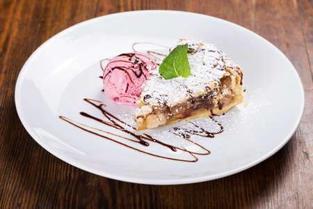 mint leaf: on the table a plate of fruit pie, sprinkle with powdered sugar with mint leaf, ball pink ice cream, with chocolate syrup Stock Photo