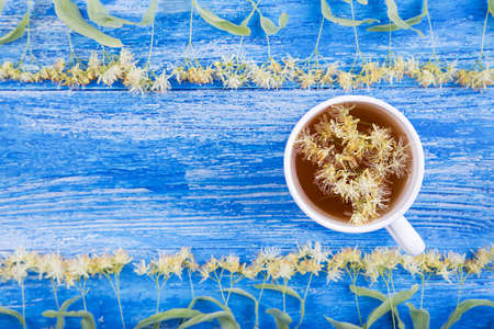 Linden tea in a cup on a wooden background. Around scattered fragrant linden flowers
