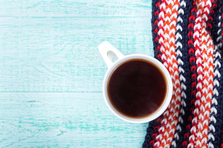convalesce: cup of hot black tea with steam in  knitted scarf. view from above
