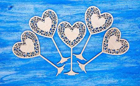 carved wooden heart on Valentines Day, with space for text on a blue wooden background