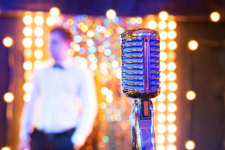 Professional retro microphone on a festive background bokeh, party with singing Banco de Imagens
