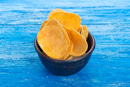 potato chips in an earthenware dish, plate stands on a blue wooden background. beer snack, unhealthy eating
