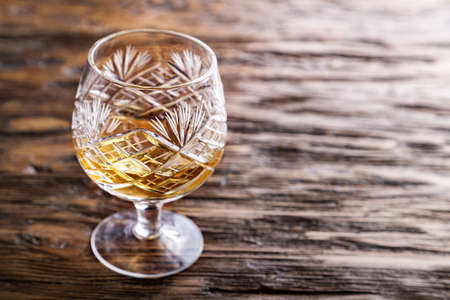 snifter: crystal glass with cognac on a wooden background, evening relaxation