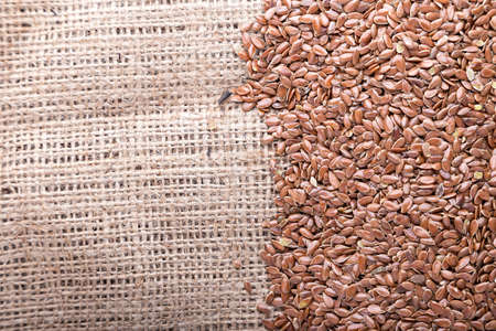 a scattered fresh raw buckwheat; on burlap background; with space for text 免版税图像