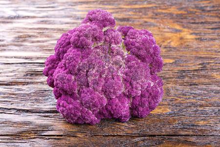 Purple cauliflower on a wooden board, diet, autumn harvest