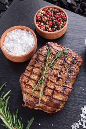 cooked steak on a black slate board, standing next to the salt, pepper, rosemary and thyme