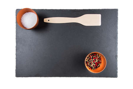 spices and scapula on black slate blackboard, with space for text
