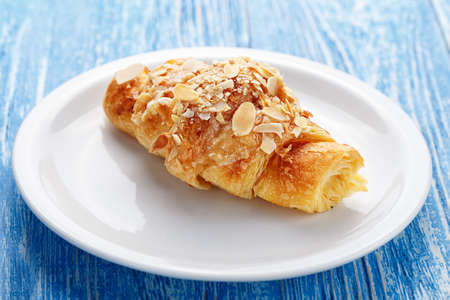 Traditional French breakfast croissant with almonds on a plate, on a wooden blue background Stock Photo