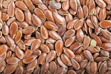a lot of flax seeds are scattered as a background, close up Stock Photo