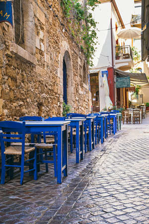 Empty cafe tables in the street in Greece, Crete, Chania. April 30, 2013 Editorial