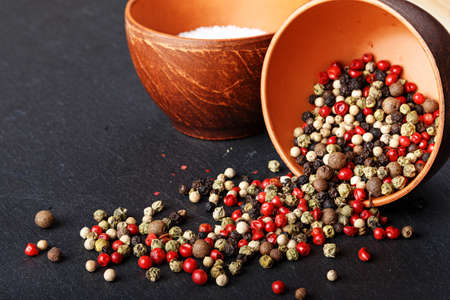 peppar: salt and pepper in a clay bowl on a slate board, pepper is scattered Stock Photo