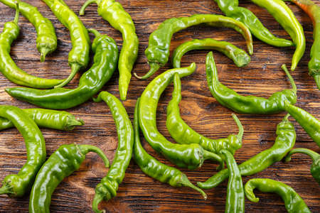 a lot of green chili peppers on a vintage wooden background