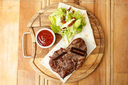 cooked steak on a pita, a wooden board, standing next to a gravy boat with ketchup and greens