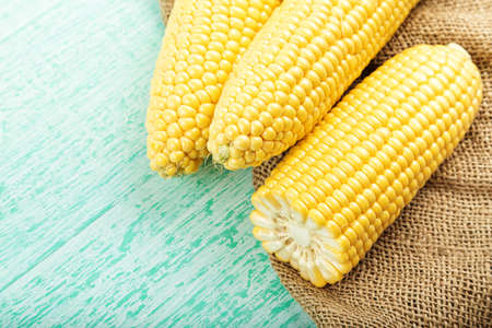 three raw corn in a clay plate on a blue background on a napkin, with space for text Stock Photo