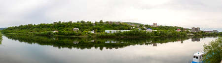 city park boat house: View from the banks of the Dniester River in Mogilev-Podolsky, Ukraine, on Moldovan houses on the opposite bank of the river, horizontal photo