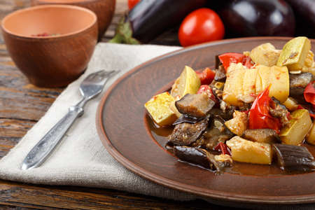 Vegetable stew with tomato, eggplant, zucchini, onion, carrot, pepper, close-up on a clay plate. Horizontal Stock Photo