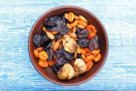 Dried figs, dried apricots and prunes in a mix with almonds in a clay plate on a wooden table, horizontal photo