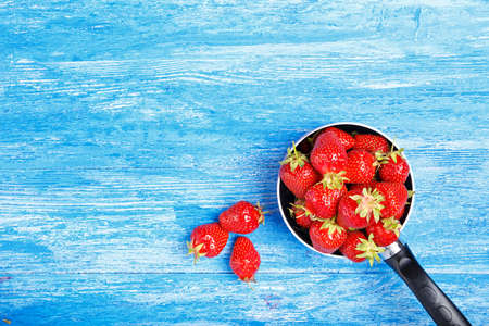 Fresh strawberry in a saucepan on a blue wooden background. Stock Photo