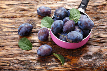 Ripe plums on a brown wooden table, healthy food, summer crop.