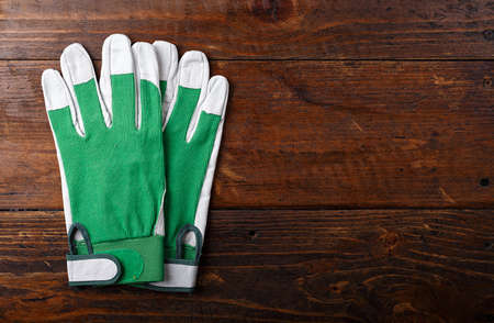New and clean construction gloves on a wooden background, space for text, horizontal photo