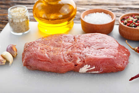 raw steak on a kitchen board with spices - salt, pepper, herbs, garlic and olive oil