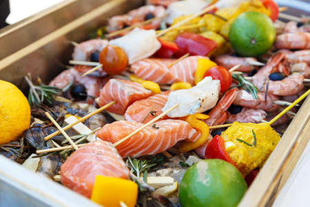 Tray with raw prawns and shish kebab from salmon with lemon and lime