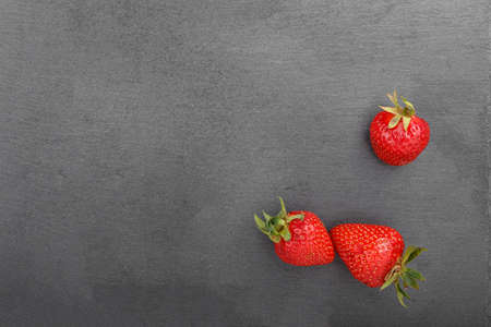 Ripe strawberry on black background of slate board, space for text, top view Stock Photo